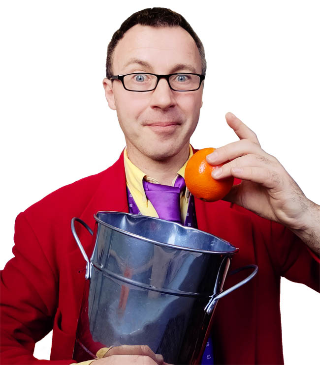 A smiling magician places an orange into a compost bucket for a school's show about sustainability